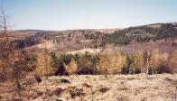 Červená Jáma - pohled na hájovnu a místa, kde se kdysi rozkládala hornická osada, jaro 2002. Vyfoceno z vrcholu kopce Homolka (844 m), ležícího zhruba 0,5 km jihovýchodně od myslivny. V pozadí v pravé části snímku úbočí Medvědí skály.