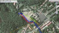 """Obr.1: Letecký pohled na areál se značením ( budovy zodpovídají mapce 4 ) Obrysy zbořené továrny jsou na fotografii ještě zřetelně rozpoznatelné.  Modrá barva - staré hlavní kryté koryto potoka Červená barva - současné nově budované koryto Černá barva - část náhonu používaná Hnědá barva - část náhonu již dávno nepoužívaného Zelená barva - propojka náhonu směrem k hlavnímu korytu potoka Žlutá barva - """"tajná"""" objevená klenbová chodba vedoucí do staré přádelny"""
