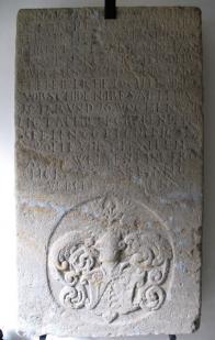 """Náhrobník Anny Dreisigové (v. 166 cm, š. 86 cm) s vtesaným nápisem v kapitále ( písmena 2,5 cm - 4cm). Nápis po obvodu náhrobníku zní takto """" ANNO 1611 DEN.2.8 MARTZI ZW/ ISCHEN 4 VND 5 VHR AVFFEN ABENT IST DIE TUGEN(D)SAME FRAVE / AN...HER / N VEIT DREIISIGS EHELICHE HAVSFRAVE IN GOTT SELIGKLICH /"""" pokračující nápis v poli uprostřed náhrobníku následovně : """"ENSTSCHLAFFEN DERER SELEN / GOTT GENADE VND EINE FROLIC/HE AVFFERSTEHVNG AM IVNG/ STEN TAGE ZVM EWIGEN LE/BEN VORLEIHN WOLLE / AMEN / IOHANNES AM 3 / ALSO HAT GOTT DIE WELT/ GELIEBET DAS ER SEINEN / EINIGEN GEBORNEN SOHN/ GAP AVF DAS ALLE DIE AHN / IHN GLEVBEN NICHT VER/LOHREN WERDEN SOND/ ERN DAS EWIGE LEBEN / HABEN""""."""