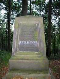 Jelení pomník, čelní stěna, stav na jaře 2001. Z nápisu je na fotografii zřetelná jen část, kterou kdosi v červnu 1999 zvýraznil bílou barvou. V pozadí je patrná silueta Jánského vrchu