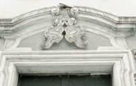 Nadpraží kostela zdobí znaky oseckého opatství vytesané v oválných polích kartuší.