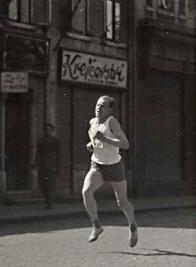 Emil Zátopek v roce 1948 na náměstí Míru před krejčovstvím pana Fořta, čp. 16 Snímek je z rodinného archivu paní Vlasty Fořtové, rozené Holé z Chudeřína, která se tady narodila v roce 1913.