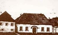 Vpravo budova školy a vlevo špitál u bývalé komendy řádu křížovníků s červenou hvězdou. Jedná se o reprodukci obrazu ze starého Mostu v roce 1870 od mosteckého malíře J. Loose