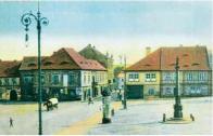 Pohled směrem od piaristického kostela na třetí náměstí kolem roku 1910. V popředí vlevo ozdobný sloup osvětlení, vpravo mariánský sloup