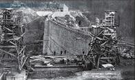Kabelový jeřáb Bleichert o rozpětí 250 m a nosnosti 2x3 t na stavbě přehrady Janov u Mostu na fotografu ze 4. 12. 1913. Levobřežní pevná věž byla společná pro obě větve jeřábu, hnací věže na pravém břehu pojížděly po obloukové kolejí. foto z časopisu Zakládání staveb.