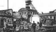 Areál dolu Julius III. po bombardování v září 1944. Na pobořených budovách v pravé části fotografie je vidět jeden Johnův obraz s postavou havíře