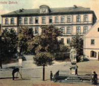 Náměstí Josefa II. se sochou císaře. Vlevo fotograf. Fotografii dominuje Německá škola