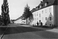 Dnešní pohled od severu na západní část ulice S. K. Neumanna, která byla za stavěna souvislou řadou jednopatrových domů s tradičně pojatými fasádami a sedlovými střechami. Pohledově oddělila Osadu od východní části Horního Litvínova